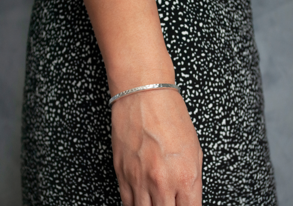 Model wearing a minimalist hammered silver cuff bracelet from Hill to Street