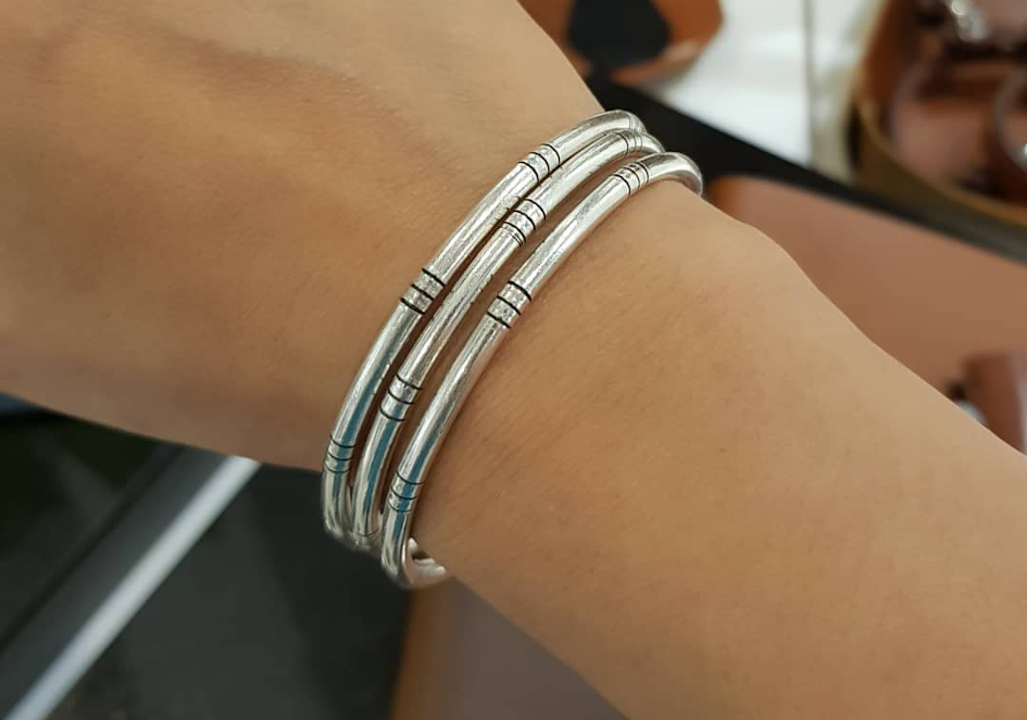 Thin silver bangles worn as stacked bracelets
