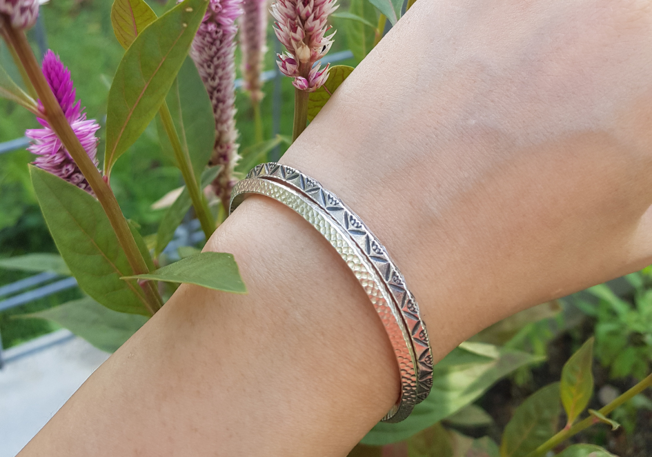 Model wearing stacked minimalist hammered triangle silver bangles
