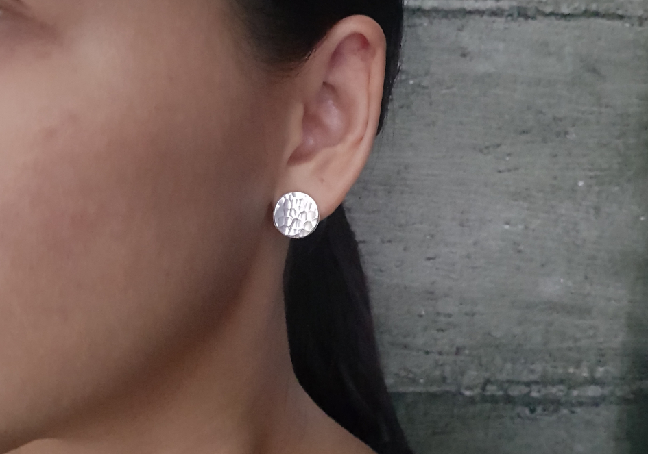 Model wearing round hammered silver stud earrings